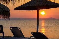 Strand-Stühle Sunbeds und Regenschirme auf dem Strand Nea Vrasna, G Stockfotografie