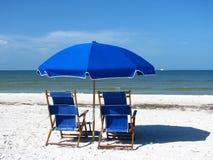 Strand-Stühle und Regenschirm Stockfotografie