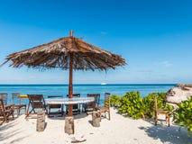Strand-Stühle und Regenschirm auf einer schönen Insel Stockfotografie
