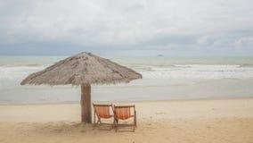 Strand-Stühle und Regenschirm auf einer Trauminsel, Panoramablick mit vielem Kopienraum Stockfotos