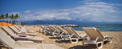 Strand, Stadt und Meerblick in Puerto Vallarta Mexiko mit Strandstühlen und Küstenlinie stockfotografie