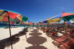 Strand-Stuhl und bunter Strand-Regenschirm Stockfotos
