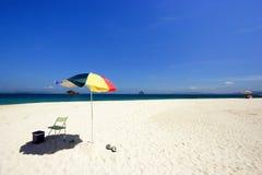 Strand-Stuhl und bunter Strand-Regenschirm Stockbild