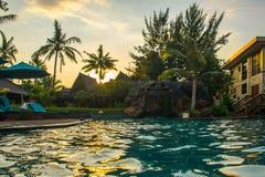 Strand sunbeds dichtbij zwembad in tropische toevlucht met palmen tijdens zonsondergang, Gili Trawangan, Lombok, Indonesië stock afbeelding