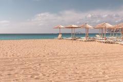 Strand sunbeds en parasols stock fotografie