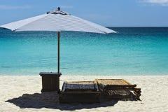 Strand-Szene mit Nichtstuer und Regenschirm Stockbilder