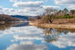 Strand und Himmel reflektiert im Fluss Lizenzfreie Stockfotos
