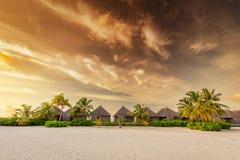 Strand und Landhäuser auf einer Insel in Malediven bei Sonnenuntergang Lizenzfreies Stockfoto
