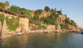 Strand und Restaurant Mermerli mit den Stadtmauern in Antalyas Oldtown Kaleici, die Türkei Stockfoto