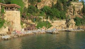 Strand und Restaurant Mermerli mit den Stadtmauern in Antalyas Oldtown Kaleici, die Türkei Stockfotografie