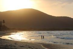 Strand und Sonnenunterganghimmel stockbilder