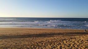 Strand und Sonnenunterganghimmel Stockbild