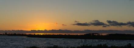 Strand und Sonnenunterganghimmel Stockfotografie