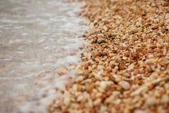 Strand - vita kiselstenar och kristallklart vatten Arkivbild