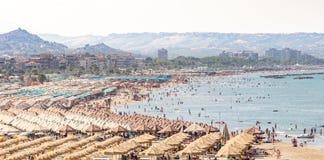 Strand voll von Sonnenschirmen und von Sesseln Stockfotografie
