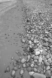 Strand von grauen Kieseln und von Felsen stockfoto