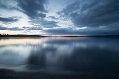Strand von ruhigem schwedischem See fotografierte in der Dämmerung Stockfoto