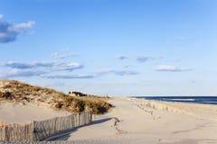 Strand-Zaun, Sand, Häuser und der Ozean. Lizenzfreie Stockfotos