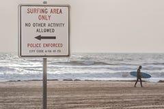 Strand-Zeichen an Virginia Beach Oceanfront With-Surfer Lizenzfreie Stockfotografie