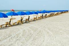 Strandaufenthaltsraumstühle mit Regenschirmen Stockfotografie