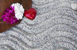 Strandbakgrund: sugrörhatt och liten röd hjärta Arkivbild