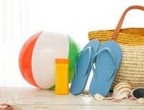 Strandbal, sunblock, wipschakelaars en zak op witte houten lijst stock afbeelding