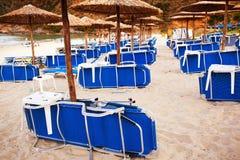 Strandbedden en paraplu's Stock Afbeeldingen