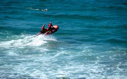 Strandbereden politie op een rode reddingsboot een surfer die dichtbij zwemmen royalty-vrije stock afbeeldingen