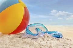 Strandboll och skyddsglasögon i sanden Fotografering för Bildbyråer