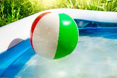 Strandboll som svävar i simbassäng i gården royaltyfria foton
