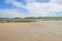 Strandcabines langs heuvelige duinen op een recreatief strand in zonlicht stock afbeeldingen