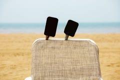 Strandchaise zitkamer van de overzeese de horizontekens die zandhemel zwart blauw adverteren stock foto