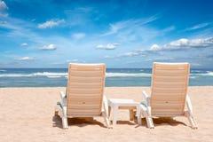 strandchaiselongues near hav två arkivbilder