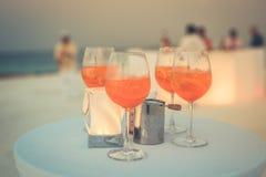 Strandcocktailgläser auf einfacher weißer Tabelle Strandfesthintergrund mit Getränken und unscharfe Leute im Hintergrund Stockbild