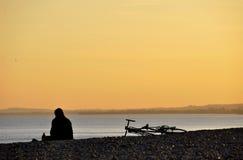 strandcykel hans sittande solnedgång för man Arkivfoto