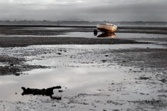 Stranded. Rowing boat stranded on tidal shore (BW royalty free stock photos