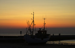Stranded. A fisherboat stranded on the beachat sunset in Lokken, Denmark Royalty Free Stock Photography