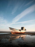 Stranded boat on the beach. In the evening royalty free stock photo