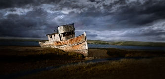 Stranded Boat. A lone boat, abandoned on land, near the ocean, dark stormy skies coming in Royalty Free Stock Photography