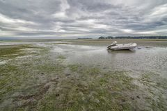 Stranded Boat on Rathtrevor Beach on a cloudy day Royalty Free Stock Images
