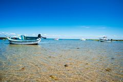 Stranded boats with water. Stranded boats on beach surrounded with water in summertime stock images