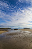 Stranded boats on a low tide beach and blue sky Royalty Free Stock Image