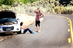 Stranded Car Trouble. Two girls needing help with car trouble stranded along side of  a remote deserted road in the  middle of nowhere. Selective focus, shallow Stock Photo