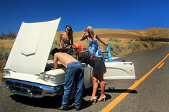 Stranded Car Trouble. Three pretty party girls needing help with car trouble, stranded along side of a remote deserted road in the  middle of nowhere, with a Stock Photos