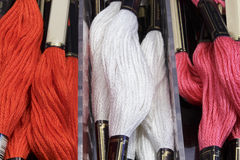 Stranded cotton threads of several colors (red, white and pink) Royalty Free Stock Photo