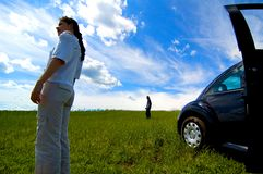 Stranded Couple. Woman and man stranded in a field with a disabled car Royalty Free Stock Photo