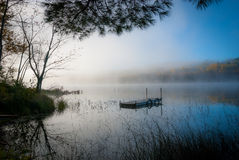 Stranded.  a swimming dock sits in still foggy water on a Northern Ontario lake. Dock sits alone in the morning at the edge of the lake.  Sunlight through fog Stock Photo
