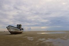 Stranded fishing boat. After a storm on the beach at Grado, Italy royalty free stock photography