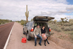 Stranded and out of gas. Two people are stranded on the side of a remote desert road out of gas stock photography