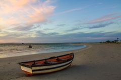 Stranded. Photo of a little boat lying on a beach at sunset Royalty Free Stock Photography